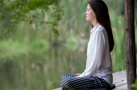 A young woman practicing Vipassana meditation