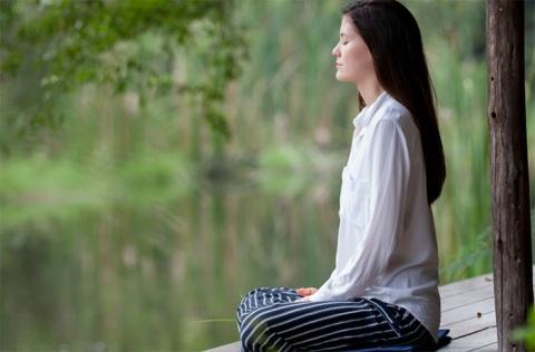 A young woman practicing Vipassana meditation